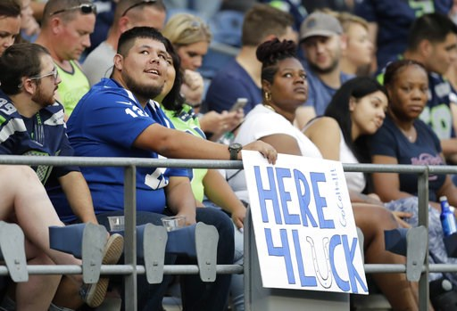 """(AP Photo/Stephen Brashear). A fan holds a sign that reads """"Here 4 Luck"""" in support of Indianapolis Colts quarterback Andrew Luck during the first half of an NFL football preseason game against the Seattle Seahawks, Thursday, Aug. 9, 2018, in Seattle."""