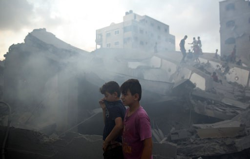 (AP Photo/Khalil Hamra). Palestinians inspect the damaged building of Said al-Mis'hal cultural center after it was hit bombed by an Israeli airstrike in Gaza City, Thursday, Aug. 9, 2018.  The Palestinian Health Ministry says several bystanders were wo...