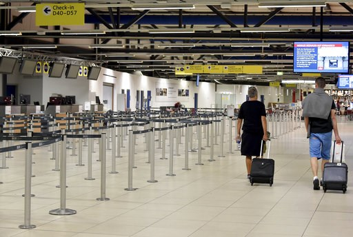 (Bernd Settnik/dpa via AP). Passenger walk through the empty departure hall of the Schoenefeld airport near Berlin Friday, Aug. 10, 2018 when several flights of Irish Ryanair airline had been cancelled due to a strike of pilots.