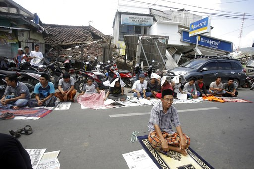 (AP Photo/Firdia Lisnawati). Villagers attend Muslim Friday prayer in front of the damage buildings in North Lombok, Indonesia, Friday, Aug. 10, 2018. The north of Lombok was devastated by the powerful quake that struck Sunday night, damaging thousands...