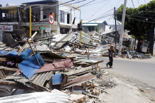 (AP Photo/Firdia Lisnawati). A man walks past destroyed buildings in North Lombok, Indonesia, Friday, Aug. 10, 2018. The north of Lombok was devastated by the powerful quake that struck Sunday night, damaging thousands of buildings and killing a large ...