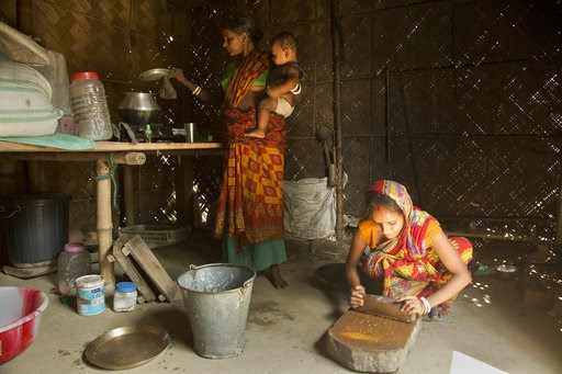 (AP Photo/Anupam Nath). In this Thursday, Aug. 9, 2018 photo, Pratima Namo Das, 22, right, and her mother-in-law Tara Namo Das, 45, cook inside the family house in Mayong, 45 kilometers (28 miles) east of Gauhati, India. A draft list of citizens in Ass...