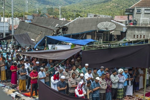 (AP Photo/Fauzy Chaniago). Muslim men perform Friday prayer as houses ruined by Sunday's earthquake are seen in the background at a makeshift mosque in Pamenang, Lombok Island, Indonesia, Friday, Aug. 10, 2018. The north of the popular resort island ha...