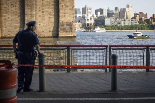(AP Photo/Robert Bumsted, File). FILE - In this Aug. 5, 2018, file photo, a New York Police Department officer stands guard as authorities investigate the death of a baby boy who was found floating in the East River near the Brooklyn Bridge in the Manh...