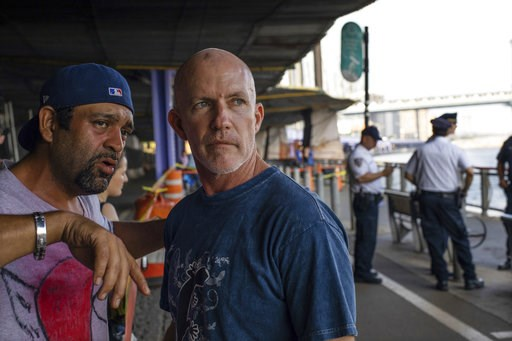 (AP Photo/Robert Bumsted, File). FILE - In this Aug. 5, 2018, file photo, Monte Campbell, of Stillwater, Okla., right, stands under the Brooklyn Bridge in the Manhattan borough after jumping into New York's East River to rescue a baby floating in the E...