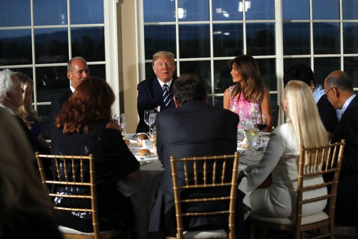 (AP Photo/Carolyn Kaster). President Donald Trump sits with first lady Melania Trump as he meets with business leaders, Tuesday, Aug. 7, 2018, at Trump National Golf Club in Bedminster, N.J.