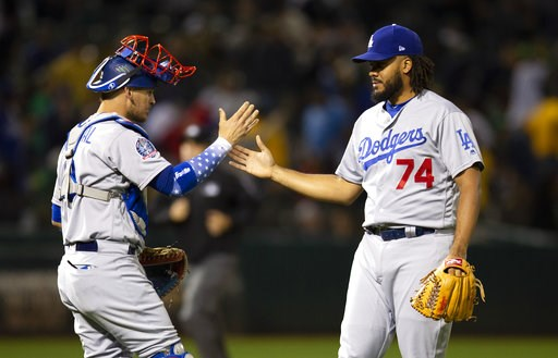 (AP Photo/D. Ross Cameron). Los Angeles Dodgers catcher Yasmani Grandal (9) and pitcher Kenley Jansen (74) celebrate the team's 4-2 victory over the Oakland Athletics in a baseball game, Tuesday, Aug. 7, 2018, in Oakland, Calif.
