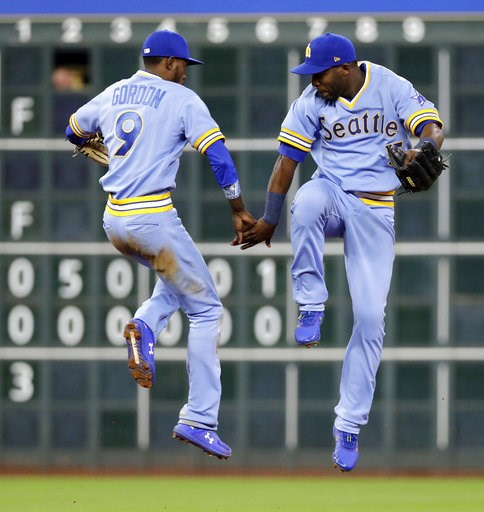 (AP Photo/David J. Phillip). Seattle Mariners' Dee Gordon (9) and Guillermo Heredia celebrate after the Mariners' 5-2 win in a baseball game against the Houston Astros on Friday, Aug. 10, 2018, in Houston.