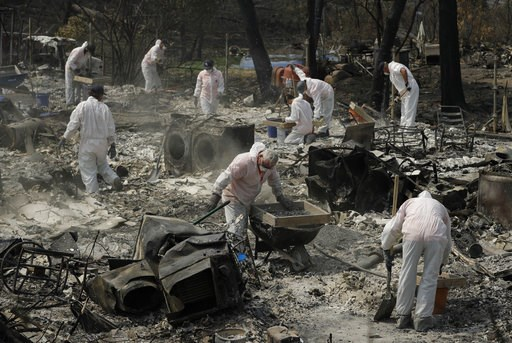 (AP Photo/John Locher). Volunteers with Samaritan's Purse sift through the charred remains of a home burned in the Carr Fire, Friday, Aug. 10, 2018, in Redding, Calif.