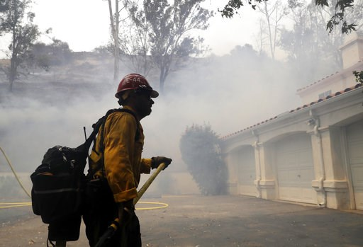 (AP Photo/Marcio Jose Sanchez). A firefighter walks in front of a home as smoke from an advancing wildfire fills the air Friday, Aug. 10, 2018, in Lake Elsinore, Calif. Firefighters are protecting foothill neighborhoods in the city of Lake Elsinore nea...