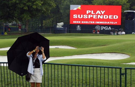 (AP Photo/Charlie Riedel). A patron takes a photo as play was suspended for the rest of the day during the second round of the PGA Championship golf tournament at Bellerive Country Club, Friday, Aug. 10, 2018, in St. Louis. Play was suspended due to he...