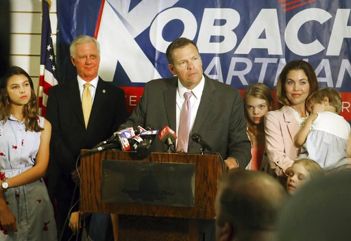 (Thad Allton /The Topeka Capital-Journal via AP). Secretary of State Kris Kobach, surrounded by his family and running mate Wink Hartman, talked to the media during a news conference at the Topeka Capitol Plaza hotel in Topeka, Kan., Wednesday, Aug. 8,...