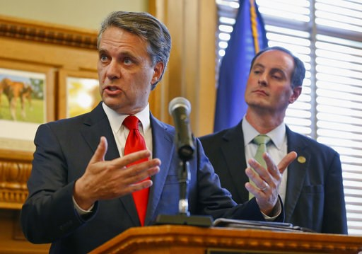 (Travis Heying/The Wichita Eagle via AP). Kansas Gov. Jeff Colyer, along with his running mate Tracey Mann, talk to reporters in Topeka, Kan., Wednesday, Aug. 8, 2018, a day after his primary race against Kansas Secretary of State Kris Kobach.