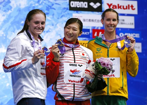 (AP Photo/Koji Sasahara). Japan's Rikako Ikee, center, poses with her medal on the podium after winning the women's 100m butterfly final, with second-placed Kelsi Dahlia of the U.S., left, and third-placed Emma McKeon of Australia during the Pan Pacifi...