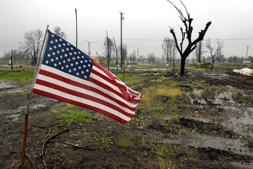 (AP Photo/Marcio Jose Sanchez, File). FILE - In this April 6, 2018, file photo, a U.S. Flag is placed on a wildfire-ravaged property as rain comes down in the the Coffey Park area in Santa Rosa, Calif.  President Donald Trump's tariffs on imported cons...
