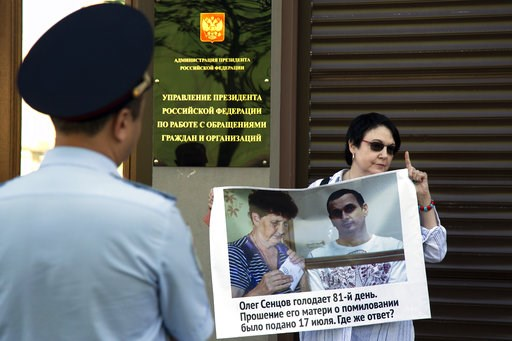 """(AP Photo/Alexander Zemlianichenko). A woman holds a poster reading """"Oleg Sentsov is on hunger strike for the 81st day. His mother lodged a petition for pardon on July 17, 2018, Where's the answer?"""" during a one-person picket in support of the jailed U..."""