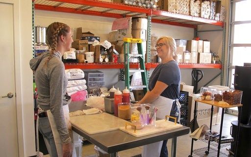 (AP Photo/Nicholas K. Geranios). In this photo taken June 8, 2018, craft donut shop owner Amy Pruchnic, right, talks with an employee at her busy new store in downtown Spokane, Wash. The state's second-largest city is booming these days thanks to a goo...