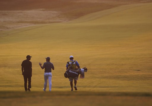 (AP Photo/Jeff Roberson). Tiger Woods, Rory McIlroy, of Northern Ireland, and caddie Harry Diamond, from left, walk out to the course to resume the second round of the PGA Championship golf tournament at Bellerive Country Club, Saturday, Aug. 11, 2018,...