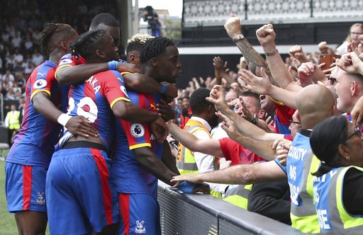 (Yui Mok/PA via AP). Crystal Palace's Jeffrey Schlupp, centre, celebrates with fans and teammates after scoring his side's first goal of the game against Fulham, during their English Premier League soccer match at Craven Cottage in London, Saturday Aug...