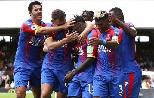 (Yui Mok/PA via AP). Crystal Palace's Jeffrey Schlupp, centre, is congratulated after scoring his side's first goal of the game against Fulham during their English Premier League soccer match at Craven Cottage in London, Saturday Aug. 11, 2018.