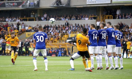 (Nick Potts/PA via AP). Wolverhampton Wanderers' Ruben Neves (left) scores his side's first goal of the game against Everton during their English Premier League soccer match at Molineux in Wolverhampton, England, Saturday Aug. 11, 2018.