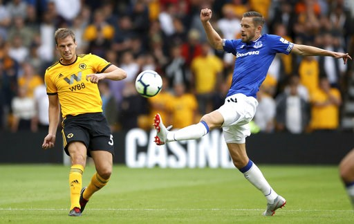 (Nick Potts/PA via AP). Wolverhampton Wanderers' Ryan Bennett, left, and Everton's Gylfi Sigurdsson during their English Premier League soccer match at Molineux in Wolverhampton, England, Saturday Aug. 11, 2018.