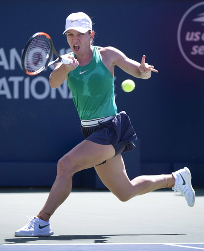 (Paul Chiasson/The Canadian Press via AP). Simona Halep of Romania returns to Ashleigh Barty of Australia during semifinals play at the Rogers Cup tennis tournament Saturday, Aug. 11, 2018 in Montreal.