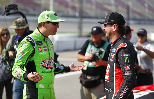 (AP Photo/Paul Sancya). Kyle Busch, left, talks with his brother Kurt Busch before qualifications for a NASCAR Cup Series auto race at Michigan International Speedway in Brooklyn, Mich., Friday, Aug. 10, 2018.