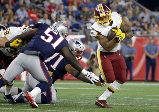 (AP Photo/Steven Senne). Washington Redskins running back Derrius Guice, right, evades New England Patriots linebacker Ja'Whaun Bentley (51) and defensive tackle Danny Shelton, center, during the first half of a preseason NFL football game, Thursday, A...