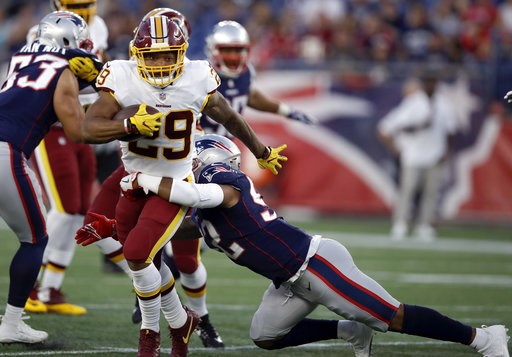 (AP Photo/Charles Krupa). New England Patriots linebacker Elandon Roberts (52) tackles Washington Redskins running back Derrius Guice (29) during the first half of a preseason NFL football game, Thursday, Aug. 9, 2018, in Foxborough, Mass.