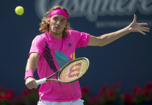 (Frank Gunn/The Canadian Press via AP). Stefanos Tsitsipas of Greece hits a backhand to Kevin Anderson of South Africa during Rogers Cup semifinal tennis tournament action in Toronto on Saturday, Aug. 11, 2018 in Montreal.