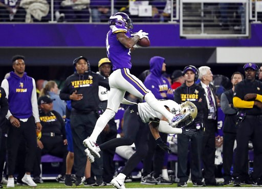 (AP Photo/Jeff Roberson, File). FILE - In this Jan. 14, 2018, file photo, Minnesota Vikings wide receiver Stefon Diggs (14) makes a catch over New Orleans Saints free safety Marcus Williams (43) on his way to the game-winning touchdown during an NFL di...