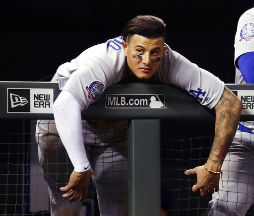(AP Photo/David Zalubowski). Los Angeles Dodgers shortstop Manny Machado hangs over the dugout rail to watch the Dodgers bat against the Colorado Rockies during the ninth inning of a baseball game Saturday, Aug. 11, 2018, in Denver. The Rockies won 3-2.