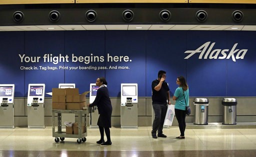 (AP Photo/Elaine Thompson). People stand in the Alaska Airlines ticket area at Sea-Tac International Airport Friday, Aug. 10, 2018, in SeaTac, Wash. An airline mechanic stole an Alaska Airlines plane without any passengers and took off from Sea-Tac Int...