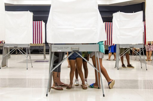 (Marie Eriel Hobro /Honolulu Star-Advertiser via AP). A family squeezes together inside of a small voting booth at Kapolei High School in Kapolei, Hawaii., Saturday, Aug. 11, 2018. The winners of most of the Democratic Party's primary races in Hawaii t...