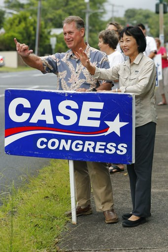 (AP Photo/Marco Garcia). Former U.S. Rep Ed Case, left, along with his wife Audrey Case, do last minute campaigning waving at passing cars, Saturday, Aug. 11, 2018, in Honolulu. Case is trying to succeed U.S. Rep Colleen Hanabusa, who is running for Ha...