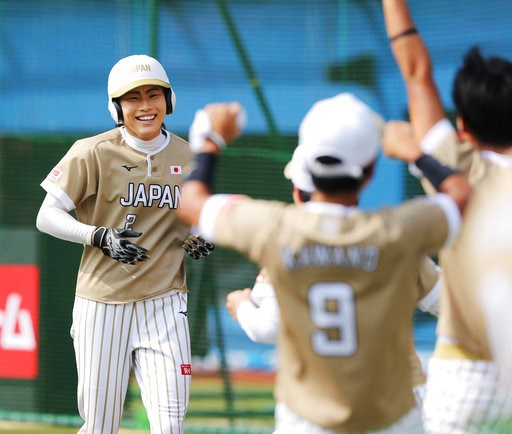 (Kyodo News via AP). Japan's Saki Yamazaki, left, is celebrated by her teammates after hitting inside-the-park home run in the third inning during their women's world softball championship game against Canada, in Chiba, near Tokyo Sunday, Aug. 12, 2018.