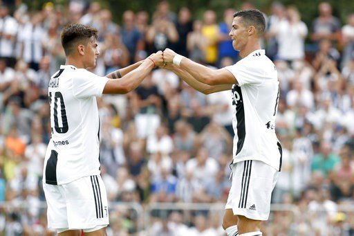 (AP Photo/Antonio Calanni). Juventus' Cristiano Ronaldo, right, touches hands with his teammate Paulo Bybala during a friendly match between the Juventus A and B teams, in Villar Perosa, northern Italy, Sunday, Aug.12, 2018.