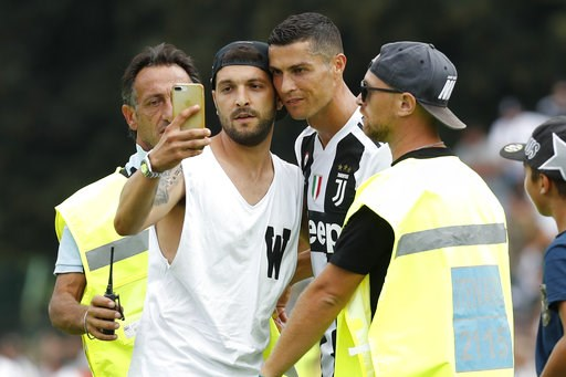 (AP Photo/Antonio Calanni). A fan takes a selfie photo with Cristiano Ronaldo during a friendly match between the Juventus A and B teams, in Villar Perosa, northern Italy, Sunday, Aug.12, 2018.