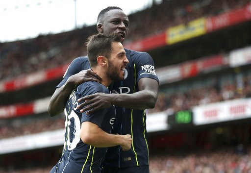 (Nick Potts/PA via AP). Manchester City's Bernardo Silva, left, celebrates with Benjamin Mendy after scoring his side's second goal of the game  during the English Premier League soccer match between Arsenal and Manchester united at the Emirates Stadiu...