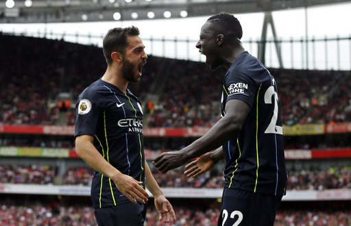 (AP Photo/Tim Ireland). Manchester City's Bernardo Silva celebrates with teammate Benjamin Mendy, right, after scoring his side's second goal during the English Premier League soccer match between Arsenal and Manchester City at the Emirates stadium in ...
