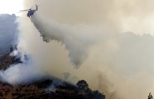 (AP Photo/Marcio Jose Sanchez). A helicopter drops water on to a wildfire Friday, Aug. 10, 2018, in Lake Elsinore, Calif.