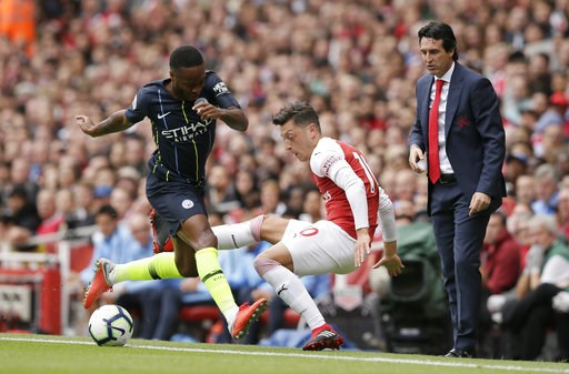 (AP Photo/Tim Ireland). Arsenal manager Unai Emery, right, watches Manchester City's Raheem Sterling, left, fight for the ball with Arsenal's Mesut Ozil during the English Premier League soccer match between Arsenal and Manchester City at the Emirates ...