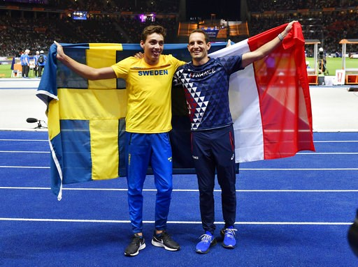(AP Photo/Martin Meissner). Sweden's gold medal winner Armand Duplantis, left, and France's bronze medal winner Renaud Lavillenie show their countries' flags after the men's pole vault final at the European Athletics Championships in the Olympic stadiu...