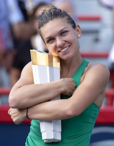 (Paul Chiasson/The Canadian Press via AP). Simona Halep, of Romania, hugs the trophy after defeating Sloane Stephens, of the United States, in the final of the Rogers Cup women's tennis tournament Sunday, Aug. 12, 2018, in Montreal.