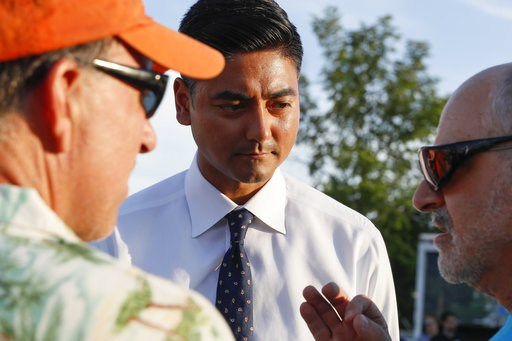 (AP Photo/John Minchillo). Hamilton County Clerk of Courts Aftab Pureval speaks with constituents as he campaigns for his 1st House District challenge against veteran Republican Rep. Steve Chabot at a music festival, Friday, June 15, 2018, in Mason, Oh...