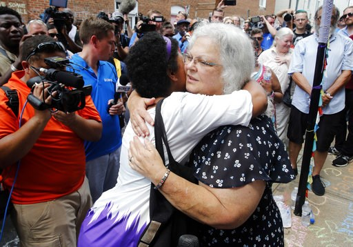 (AP Photo/Steve Helber). Susan Bro, mother of Heather Heyer who was killed during last year's Unite the Right rally, embraces supporters after laying flowers at the spot her daughter was killed in Charlottesville, Va., Sunday, Aug. 12, 2018. Bro said t...