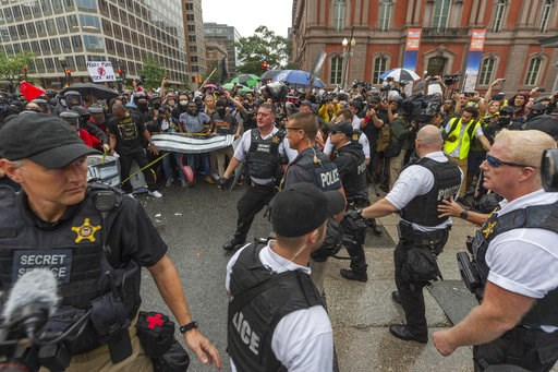 """(Craig Hudson/Charleston Gazette-Mail via AP). Metro Police and Secret Service personnel are forced back by counter-protesters outside of the Pennsylvania Avenue security barrier on 17th street while attempting to escort attendees of the """"Unite the Rig..."""