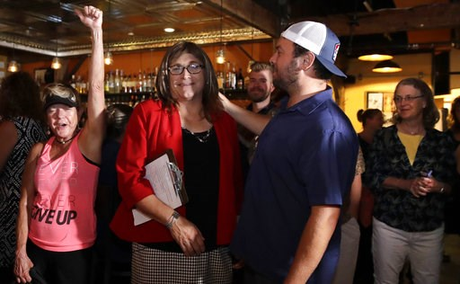 (AP Photo/Charles Krupa). Vermont Democratic gubernatorial candidate Christine Hallquist, center, a transgender woman and former utility executive, is greeted by her supporters during her election night party in Burlington, Vt., Tuesday, Aug. 14, 2018.