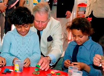 (AP Photo/Jamal Nasrallah, Pool). Britain's Prince Charles, center, sits with Syrian refugee children during his visit to the King Abdullah Park for Syrian Refugees in Ramtha city north of Amman, Jordan, Wednesday, March 13, 2013.